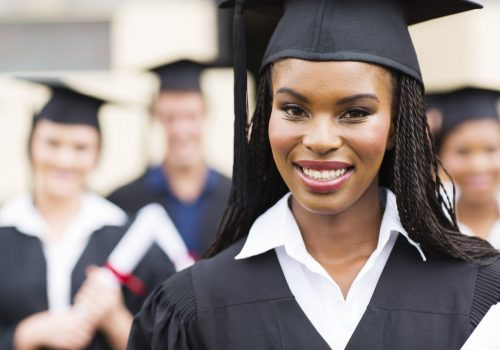 close up portrait of african american female graduate in front of classmates